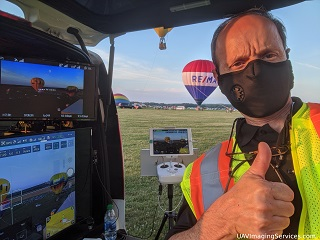 Marty, in a mask for covid-19, giving a thumbs up, with a background of the Mobile Ground Control Station and hot air balloons